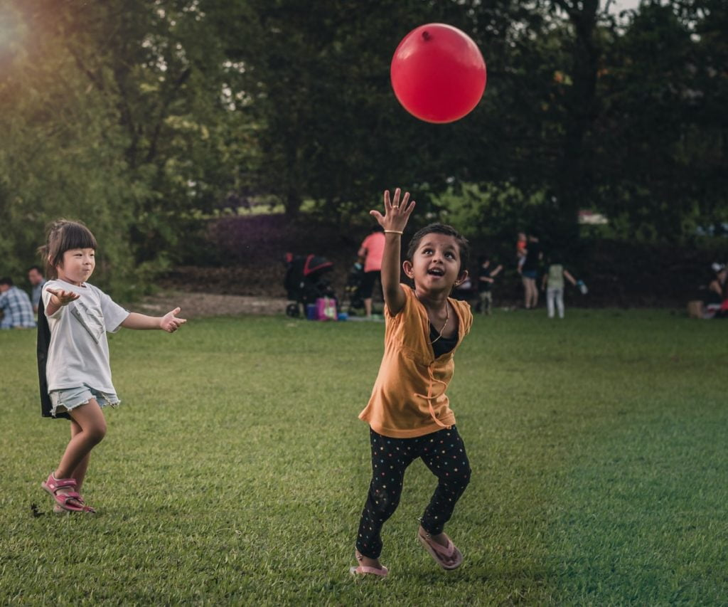 Two girls playing with a balloon in a park